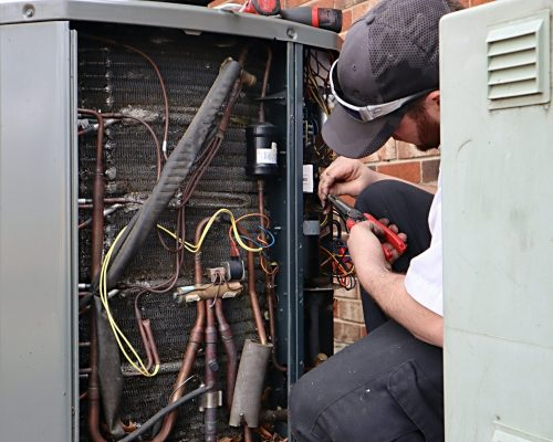 service-repair-being-done-on-a-heat-pump-hvac-syst-CUZ5KG7-min